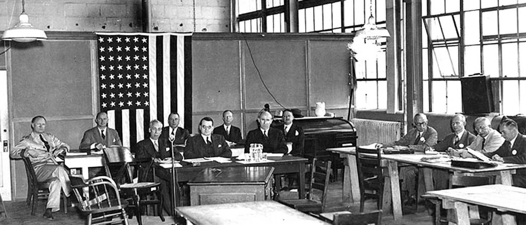 Commerce Department Inquiry, May 27, 1937. Seated at the small table in center are, left to right: R.W. Schroeder; Colonel South Trimble, Jr. (Chairman); and Dennis Mulligan. Technical advisors seated at the large table behind them are, left to right: Commander Charles E. Rosendahl, USN; Gill R. Wilson; Colonel R.B. Lincoln, U.S. Army; Lieutenant Colonel C. de F. Chandler; and Colonel H.E. Hartney. Stated at right are, left to right: G.C. Lovening, Frederick Hoffman, Dr. Hugo Eckener and Ludwig Dürr.