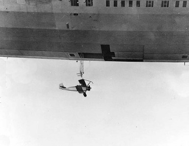 N2Y-1 training plane beneath trapeze and T-shaped opening of Akron's hangar deck